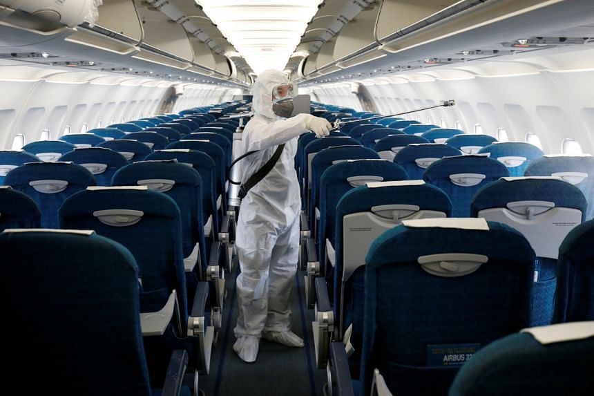 A health worker sprays disinfectant inside a Vietnam Airlines airplane at Noi Bai airport in Hanoi on Feb 21, 2020.