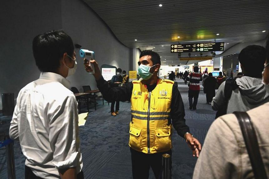 In a photo taken on Feb 23, 2020, an Indonesian health official takes temperature readings of arriving passengers amid concerns of the coronavirus outbreak at the Jakarta international Airport.