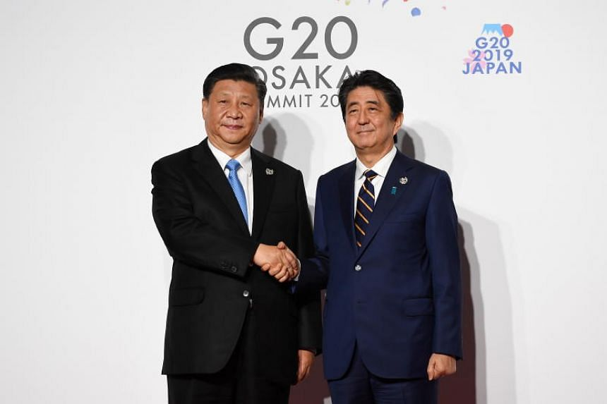 Chinese President Xi Jinping (left) is welcomed by Japanese Prime Minister Shinzo Abe on the first day of the G20 summit in Osaka, on June 28, 2019.