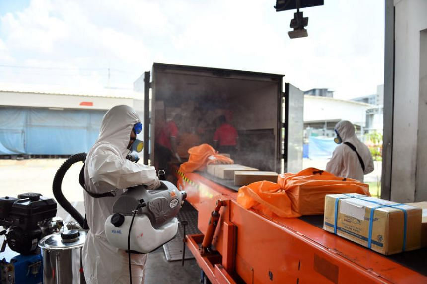 Postal workers disinfect packages arrived from overseas, to contain the spread of coronavirus in Bangkok, on March 5, 2020.