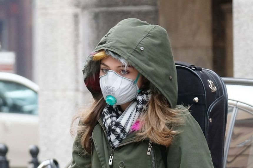 A woman wears protective face mask at the entrance of the Cremona Hospital in Milan, Italy, March 5, 2020.
