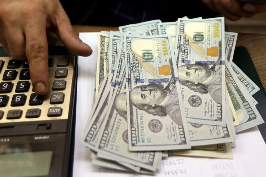 n employee counts US dollar bills at a money exchange office in central Cairo, Egypt.