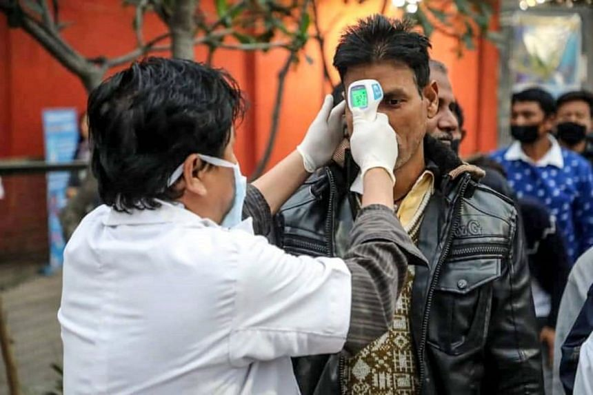 In this handout photograph released by Bhutan's Prime Minister's Office on Feb 2, 2020, a health worker conducts temperature checks at the India-Bhutan border.