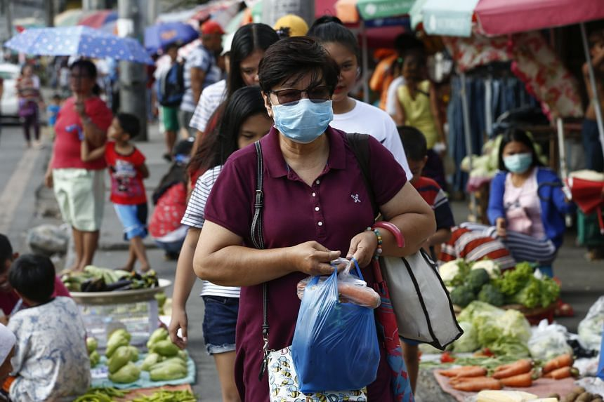 A Filipino wearing a protective mask carries a bag of vegetables at a roadside market in Quezon City, Philippines, on Feb 29, 2020.