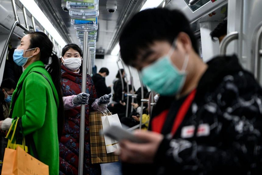 Commuters wearing face masks travel in the metro in Changsha, the capital of Hunan province, on March 5, 2020.