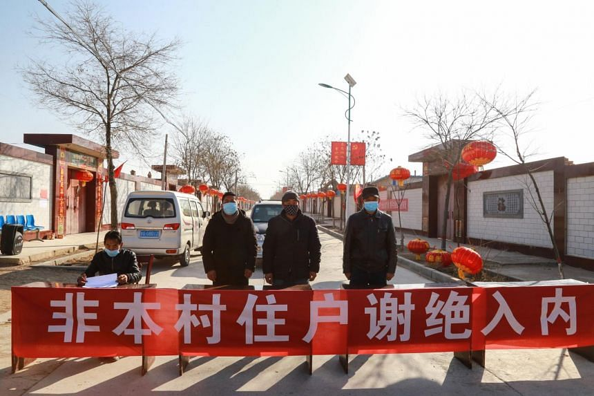 In a photo taken on Jan 27, 2020, staff members wearing face masks stand guard at a check point at the entrance of a village in China's northwestern Gansu province.