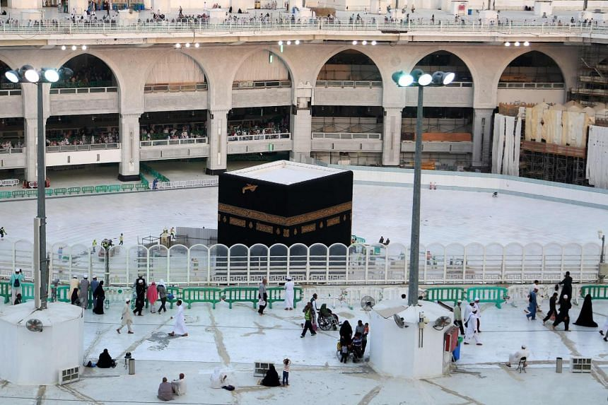 Small groups of people walk around the empty white-tiled area surrounding the Kaaba, inside Mecca's Grand Mosque.