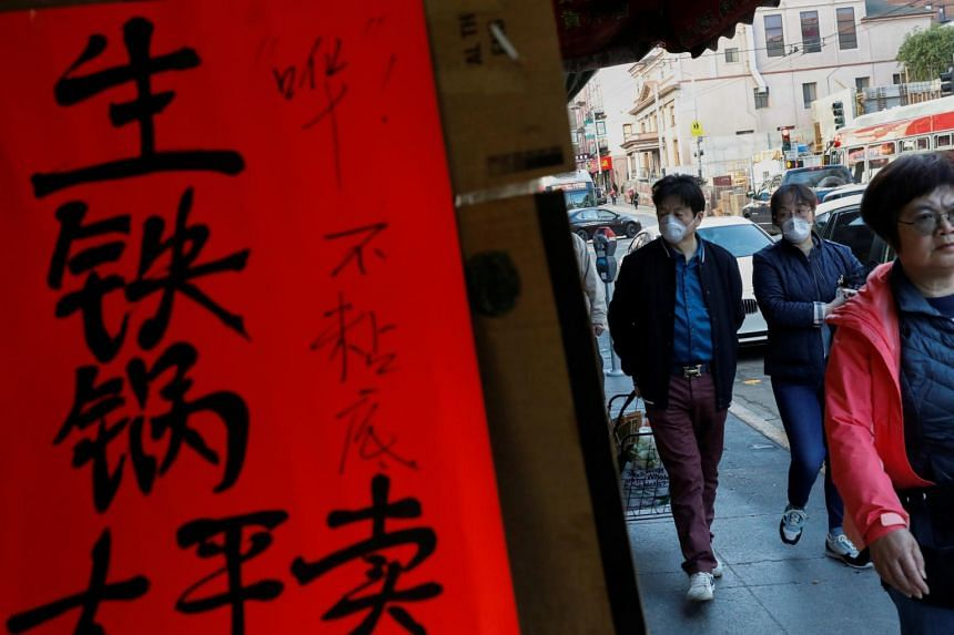 A photo taken on Feb 25, 2020 shows people with face masks walking through the Chinatown section of San Francisco.