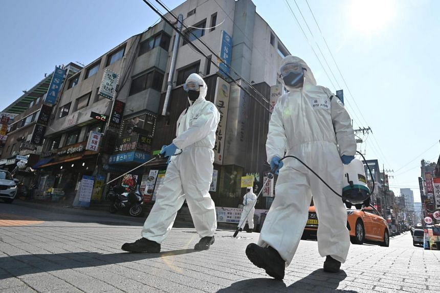 South Korean soldiers wearing protective gear spray disinfectant on the street at Gangnam district in Seoul on March 5, 2020.