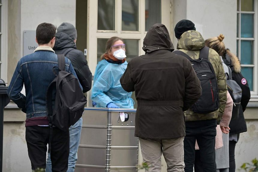 A medical employee talks with people waiting outside the new medical examination department on the grounds of the Charite university hospital's campus Virchow in Berlin, on March 4, 2020.