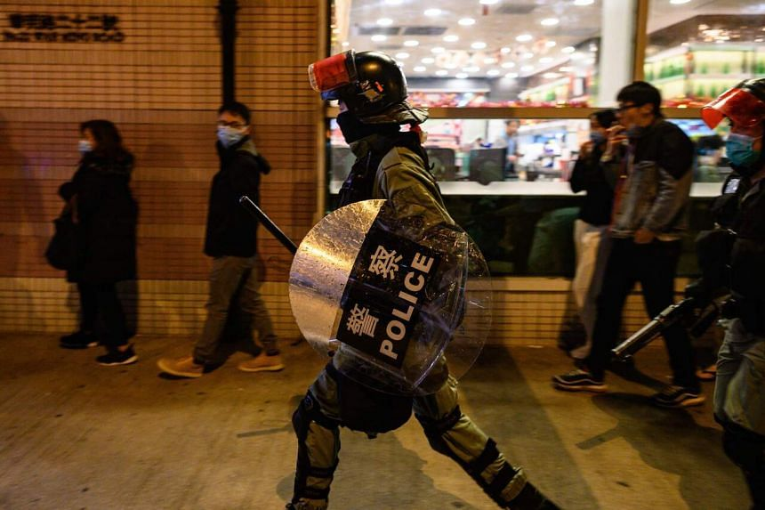 Riot police run in a residential area as residents protest in the Fanling district in Hong Kong on Jan 26, 2020.