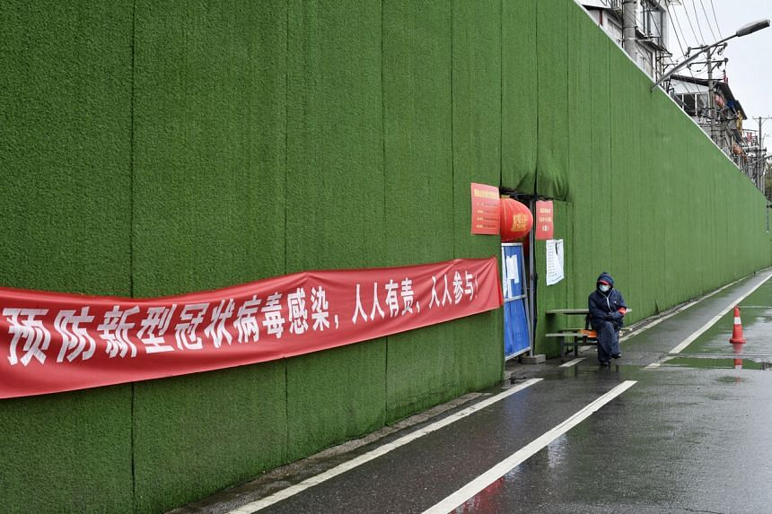 A guarded entrance to an area under lockdown in Wuhan, China. China has won plaudits for the success of its drastic containment measures, including the virtual lockdown of Hubei province.