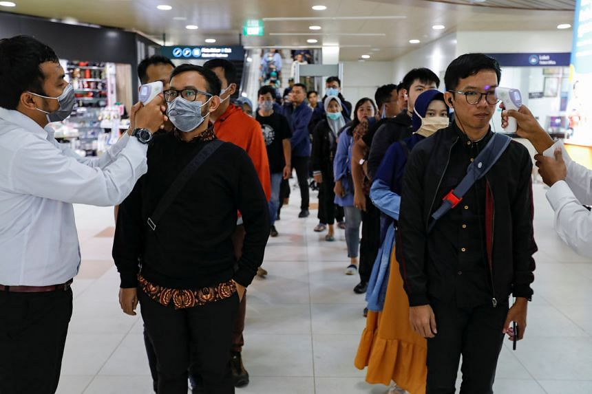 Medical officers checking passengers' temperature at a Mass Rapid Transit station in Indonesia, after the nation confirmed its first cases.
