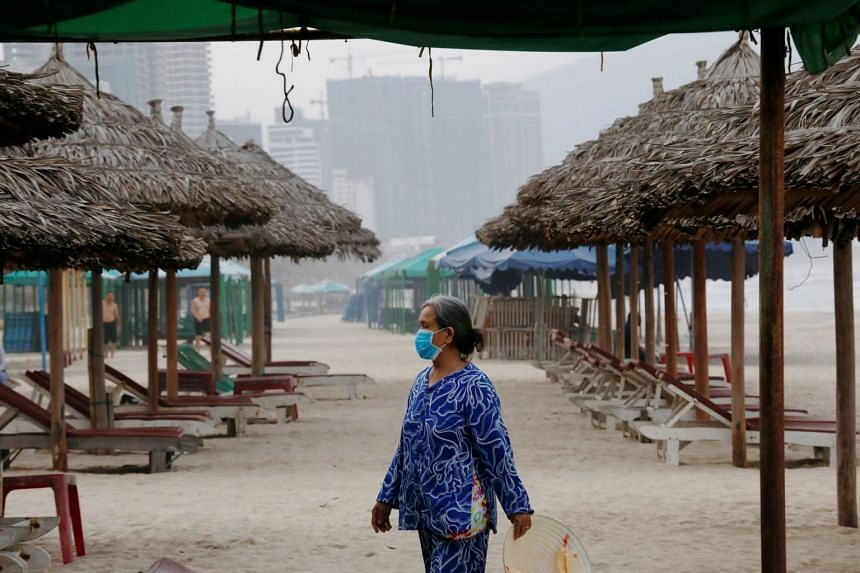 A woman wears a protective mask on a beach in Da Nang City, Vietnam.