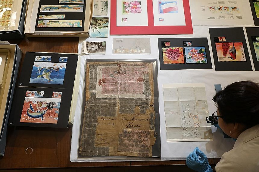 Mr Xavier Lee, third-generation owner of Loong Fatt Tau Sar Piah, which now has an NHB-funded heritage corner in its shop in Balestier. Ms Phyllis Koh, 35, a National Heritage Board conservator at the Heritage Conservation Centre, studying a letter f