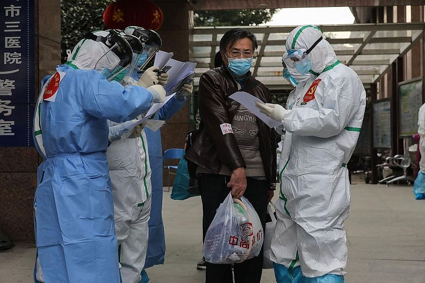 Medical staff checking information as a Covid-19 patient left a Wuhan hospital on Wednesday. Early estimates of the coronavirus death rate in China were about 2 per cent. A more updated report in the New England Journal of Medicine based on over 1,00