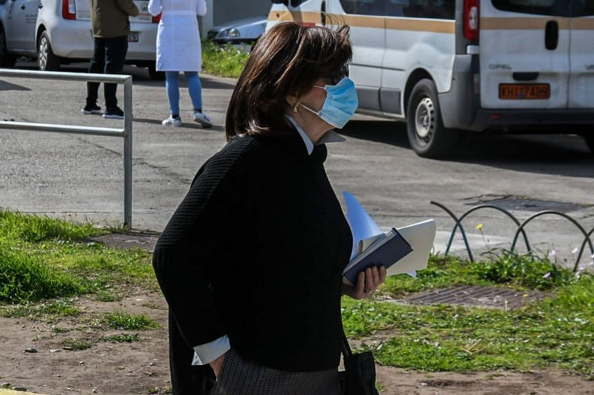 A woman wearing a protective face mask walks in front of the Patras University Hospital in southwestern Greece, where patients infected with Covid-19 are hopitalised.