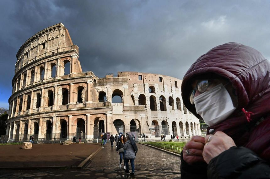 A man wearing a protective mask passes by the Coliseum in Rome on March 7, 2020.