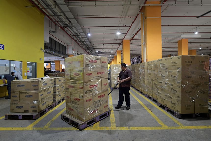 A worker unloads household consumables from a lorry at the Fairprice Benoi Distribution Centre on March 7, 2020.