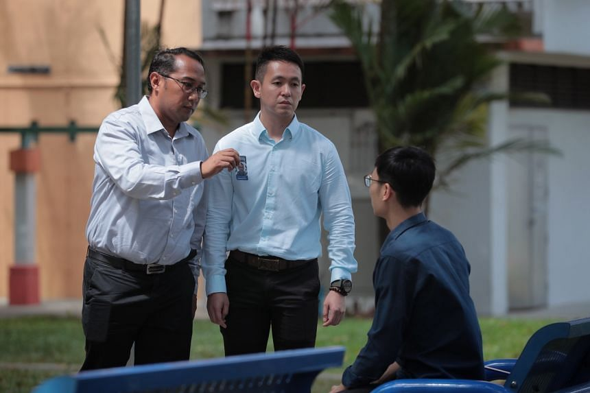 (From left) Senior Staff Sergeant Mohamad Shapie Saleh and Sergeant Loh Seng Hong re-enacting how they would conduct interviews out in the field as part of their contact-tracing duties.