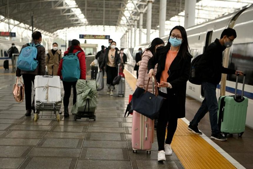 Passengers wearing face masks arriving at the Jiujiang railway station, in China's central Jiangxi province on March 8, 2020.