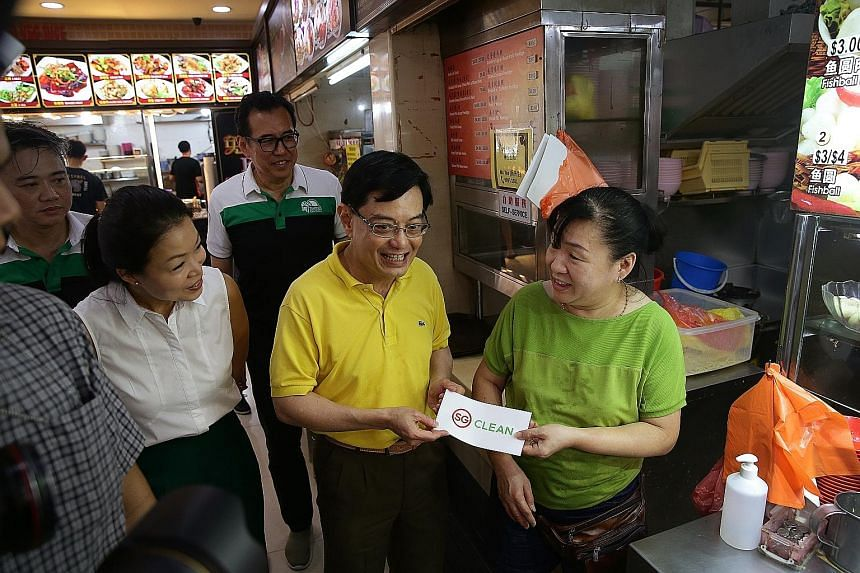 Deputy Prime Minister Heng Swee Keat and Tampines GRC MP Cheng Li Hui with Madam Lim Puay Lang, 50, owner of a minced meat noodle stall which received the SG Clean certification, at a coffee shop in Tampines yesterday. Certification means stalls have