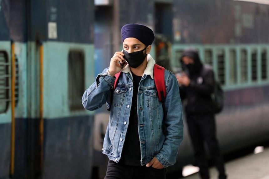 A photo taken on March 5, 2020 shows a man with a face mask, talk on his mobile phone at  railway station in Jammu, India.
