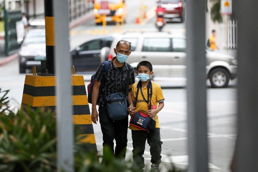 A man and a child wearing masks at Greenhills district in Manila, Philippines, on March 6, 2020.