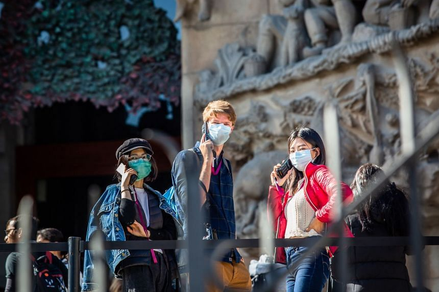 Tourists wear protective face masks as they take part in an audio tour of the Sagrada Familia cathedral in Barcelona, Spain.