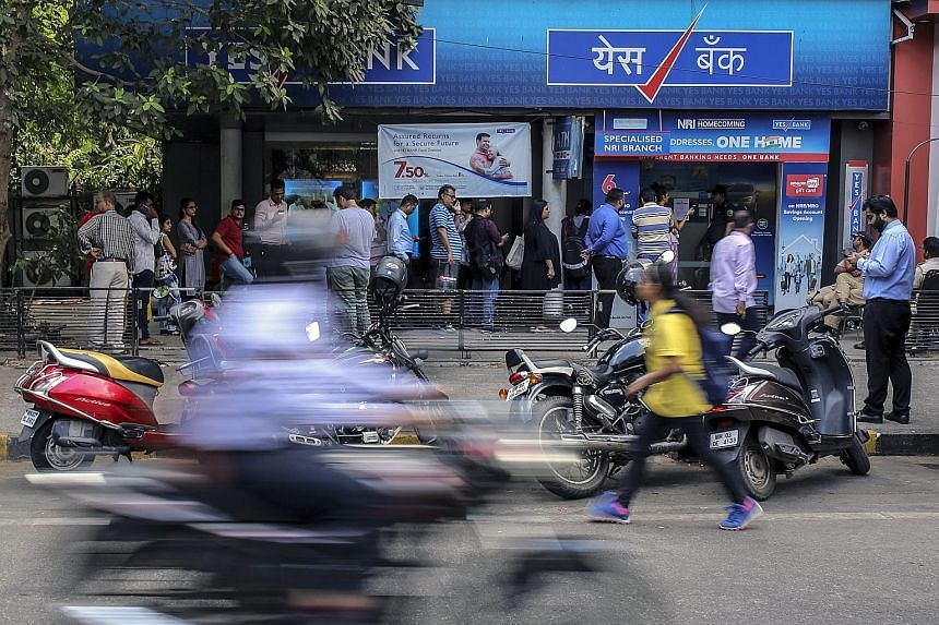 Customers standing in line outside a Yes Bank branch in Mumbai, India, last Friday. The Reserve Bank of India took to Twitter on Sunday to affirm the safety of deposits in the wake of a decision to seize Yes Bank and invite the nation's largest lende