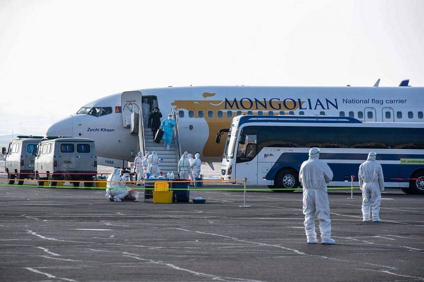 In a photo from Feb 1, 2020,  a Mongolian citizen gets off a plane after evacuating from Wuhan, in Ulaanbaatar, Mongolia.