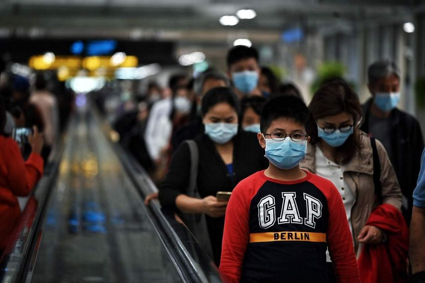 Arriving passengers with masks disembark at Suvarnabhumi International Airport in Bangkok, on Jan 24, 2020.