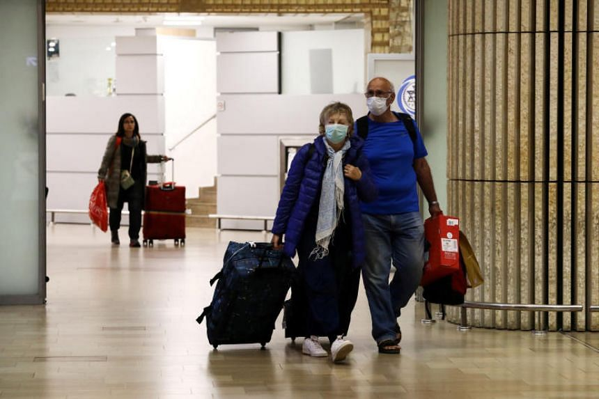 In a photo taken on Feb 22, 2020, passengers wearing protective face masks walk at the arrival area of a terminal at the Ben Gurion airport in Lod, near Tel Aviv, Israel.