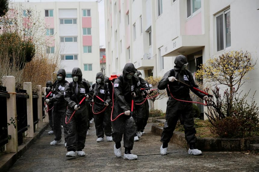 South Korean soldiers spray disinfectant at an apartment complex which is under cohort isolation after mass infection of the coronavirus was reported, in Daegu, South Korea, on March 9, 2020.