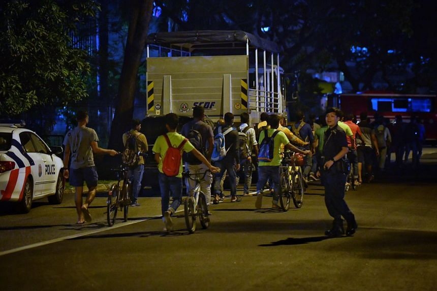 Police officers guiding the workers who were staying in dormitories near the fire site at 18 Jalan Besut, back to their quarters, on March 9, 2020.