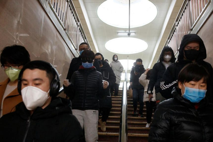 A photo taken on March 10, 2020 shows people with face masks at a subway station in Beijing.