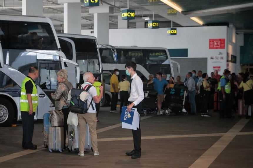 Passengers who disembarked from the Costa Fortuna cruise ship board buses at Marina Bay Cruise Centre on March 10, 2020.