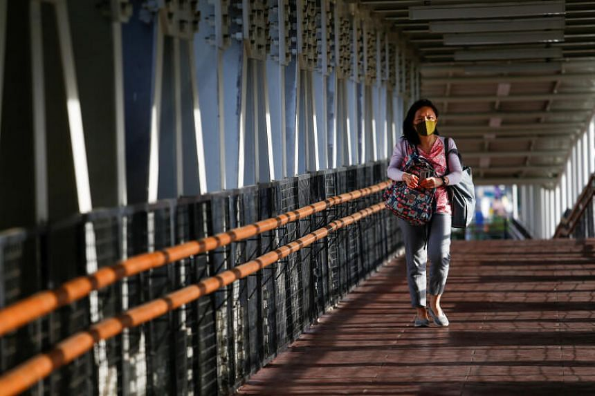 A woman wearing a protective face mask walks on a bridge in Jakarta, Indonesia, on March 9, 2020.