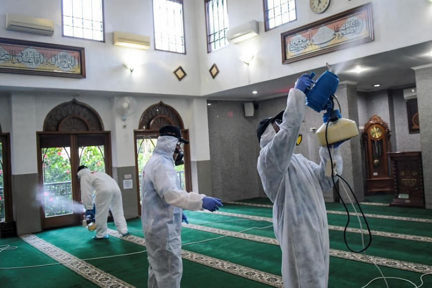 Officials spray disinfectant inside a mosque in Jakarta on March 8, 2020.