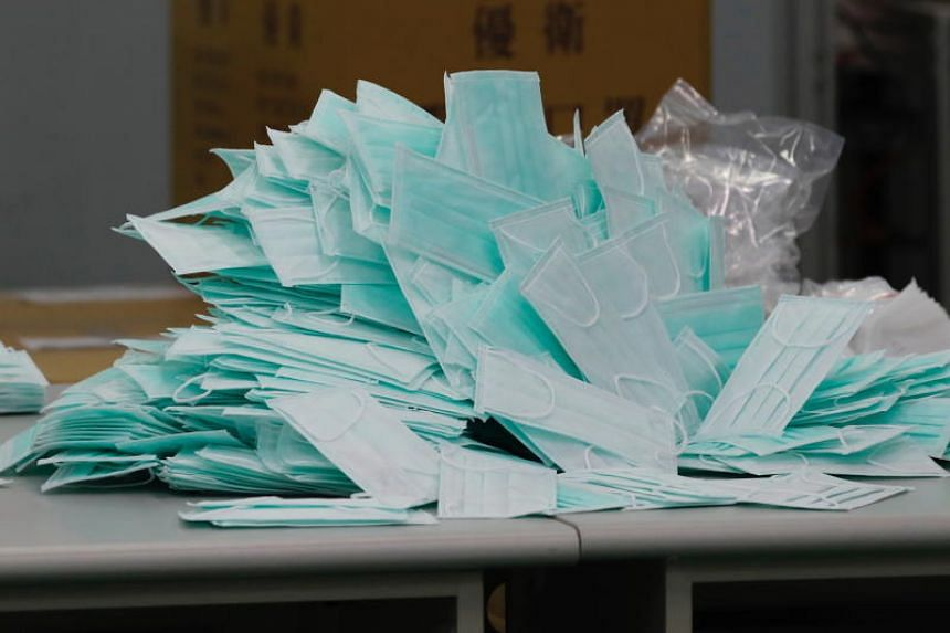 Newly finished surgical masks sit on a table inside the Universal Incorporation factory in Tainan, Taiwan, on March 6, 2020.