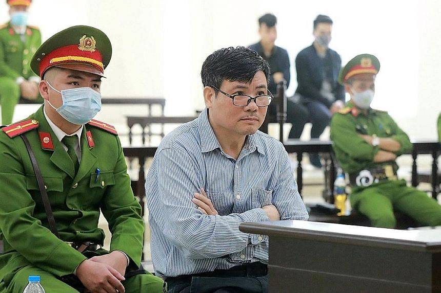 Truong Duy Nhat (centre) on trial in Hanoi on Monday. The journalist is known for his criticism of the ruling Communist Party. PHOTO: AGENCE FRANCE-PRESSE