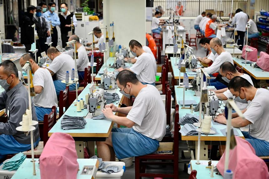 Inmates using sewing machines as they make face masks at the Taipei Prison in Taoyuan City, northern Taiwan, on March 10, 2020.