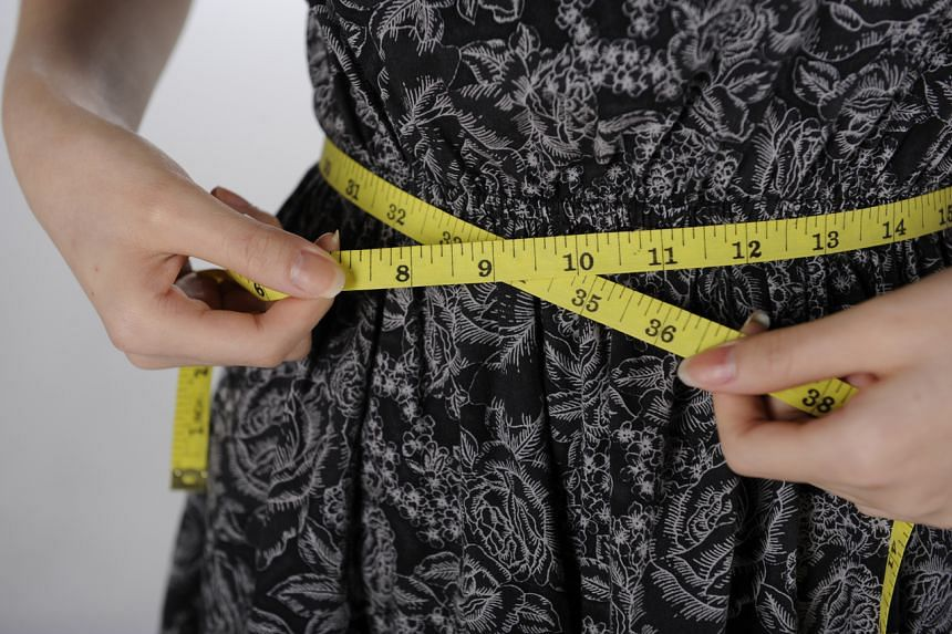 A posed photo of a woman measuring her waist with a measuring tape.