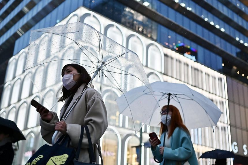 Women wearing face masks hold umbrellas as they walk down a street in Tokyo's Ginza area on March 10, 2020.