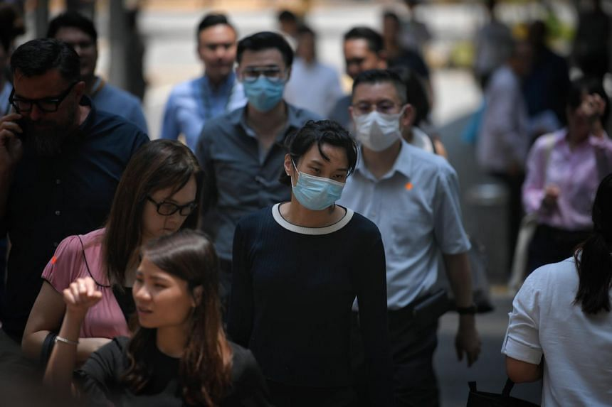 People wearing masks as they cross the road in Singapore's Central Business District on March 10, 2020.