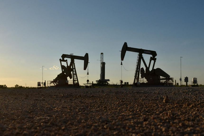 In a photo taken on Aug 22, 2018, pump jacks operate in front of a drilling rig in an oil field in Midland, Texas.