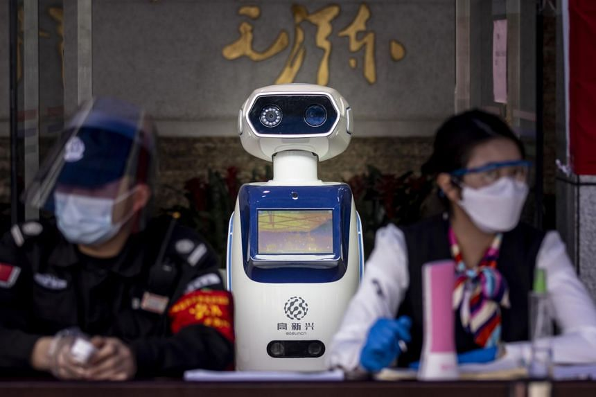 In a photo taken on Feb 26, 2020, a robot checks visitors' body temperatures at the entrance of a government building in Guangzhou, China.