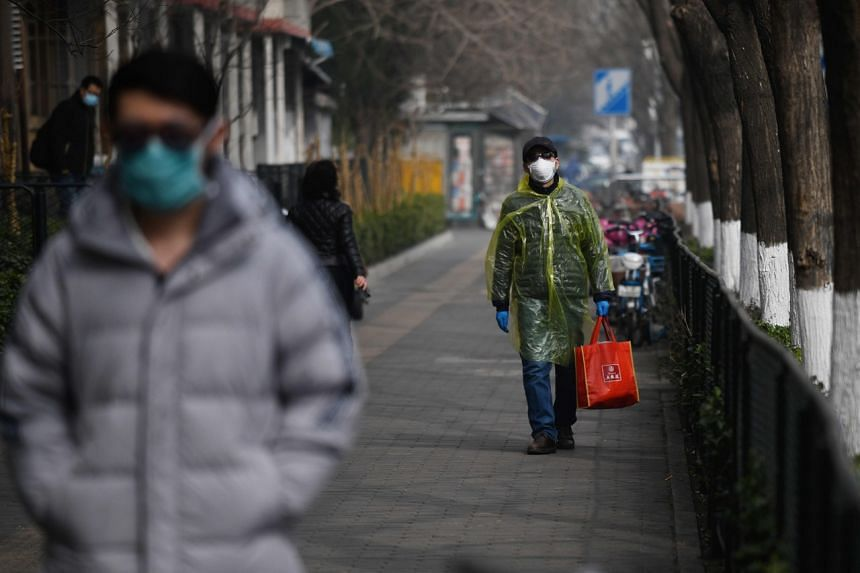 A man wears protective clothing as a preventive measure against the coronavirus as he walks outside the Peking University People's Hospital in Beijing, on Feb 21, 2020.