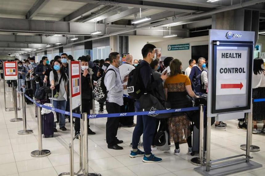 Incoming passengers lining up to have their temperatures taken and health assessed at a checkpoint at Suvarnabhumi Airport in Bangkok, on March 9, 2020.