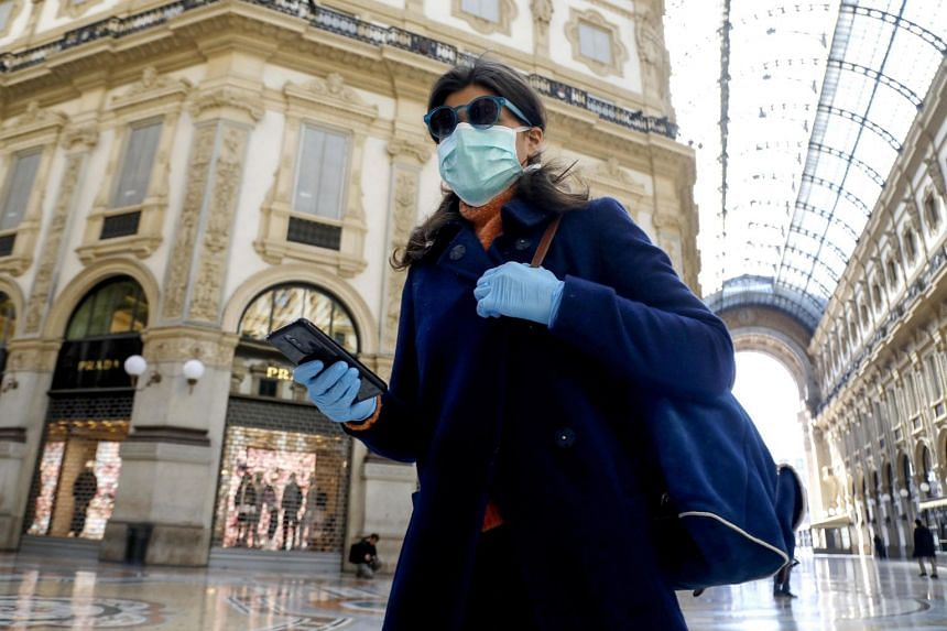 A woman walks past the deserted Galleria Vittorio Emanuele II amid the coronavirus outbreak, in Milan, Italy, March 11, 2020.